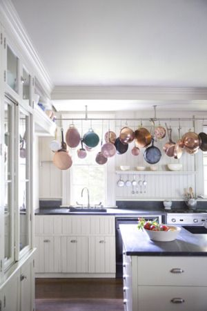 HANG POTS AND PANS ALONG THE SIDE OF THE SMALL KITCHEN