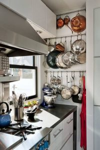 HANG POTS AND PANS CLOSE TO THE COUNTER IN SMALL KITCHEN
