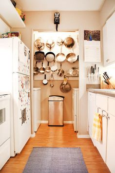 HANG POTS AND PANS HIDDEN IN THE PANTRY IN SMALL KITCHEN